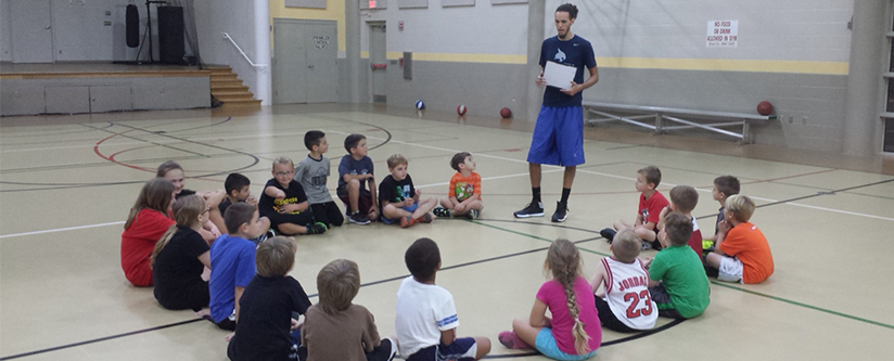 A group of kids learning about basketball from an instructor at the Rising Stars Basketball Program in North Port, Fl