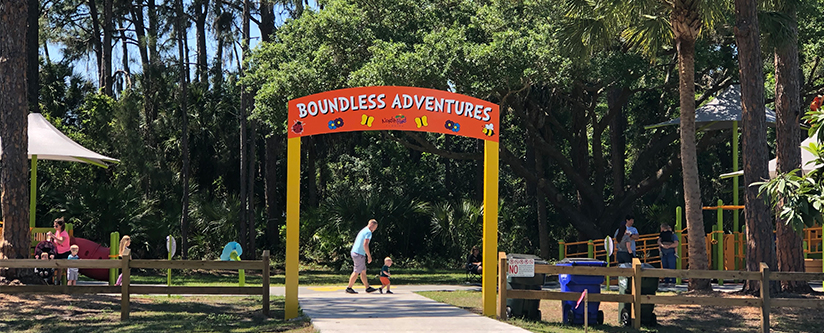 The new Boundless Playground entrance with families playing in the background in North Port, FL.