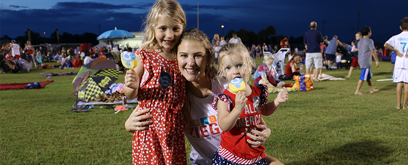 Mother hugs her young daughters as they enjoy ice cream at the North Port Freedom Festival