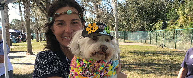 A woman poses in costume with her dog at the Annual Woofstock held at the Canine Club in North Port, Fl.
