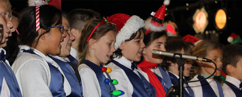 A choir sings in holiday hats from a stage.