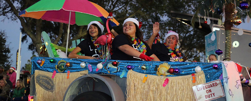 Ladies in a tropical themed float smile at the attendees.