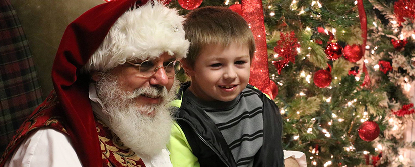 Santa poses for a picture with a young boy