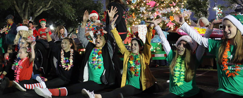 Young ladies in holiday gear cheer as the tree is lit