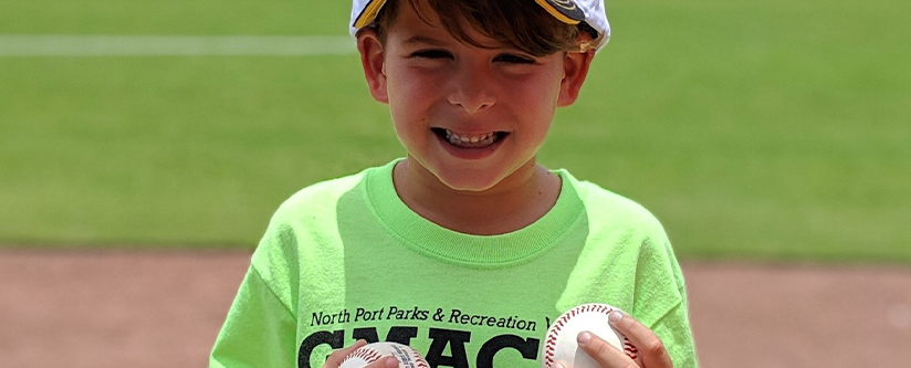 young boy smiling in the sun with baseballs at a game