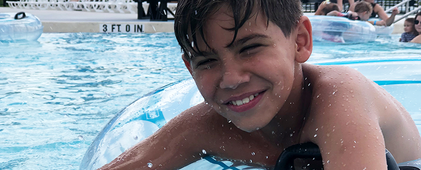 Boy smiles in inner tube on Relaxahattchee Lazy River